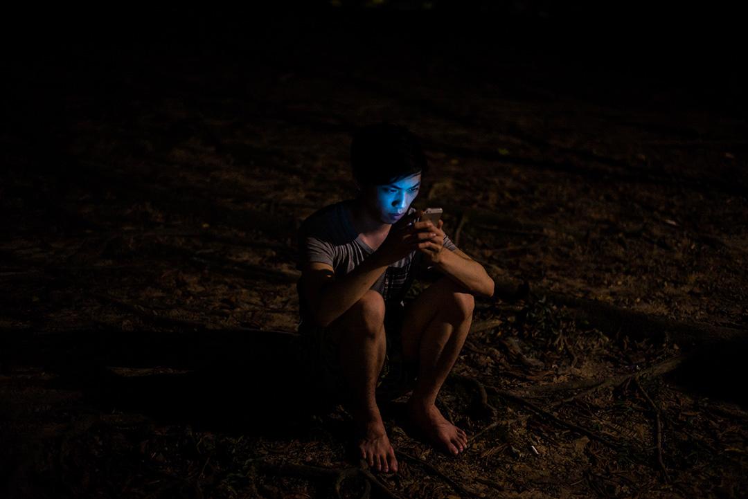 一名青年半夜赤腳在公園裏玩最新的手機遊戲。