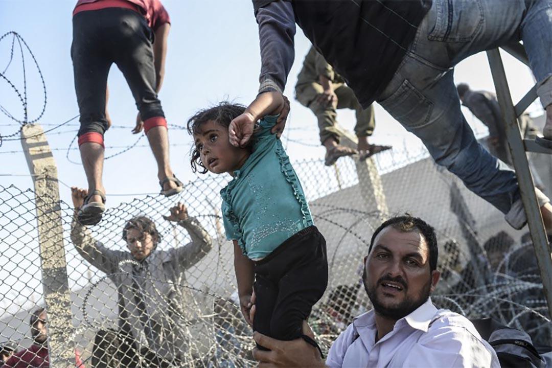 2015年6月14日,一個敍利亞兒童被抱進土耳其邊界。