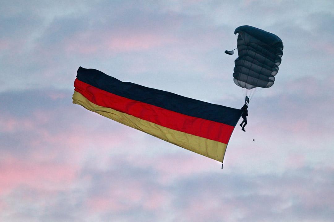 圖為兩德民主統一紀念日時德國傘兵懸著國旗跳傘。