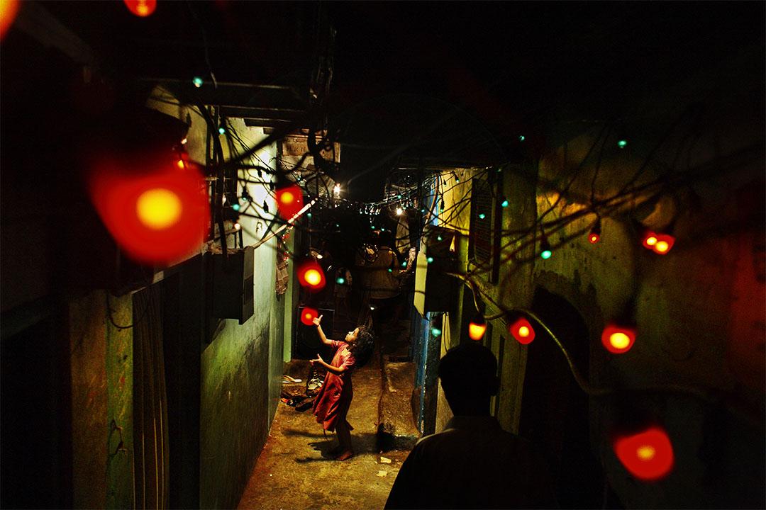 2006年,印度孟買,一戶人家高掛起結婚用的燈飾,一個女孩在紅燈下玩耍。