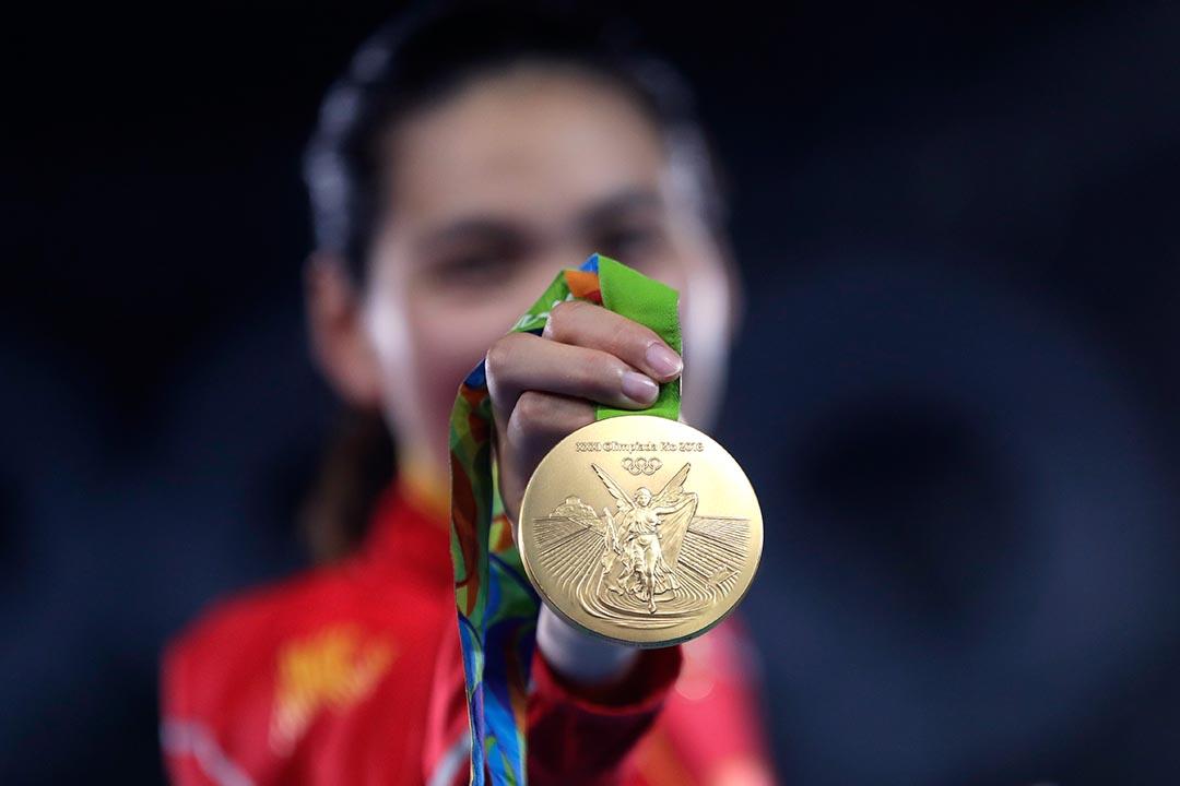 中國鄭姝音在頒獎儀式上拿著金牌慶祝。