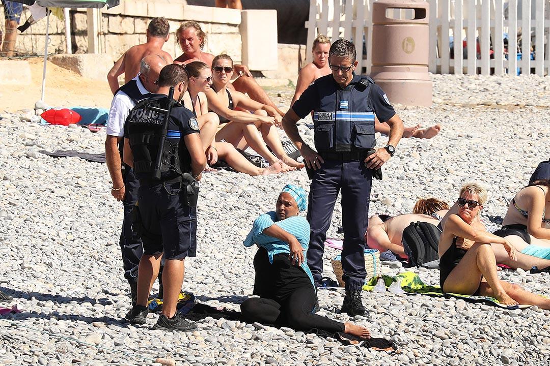 警察向一名穿著布堅尼泳衣的女人發告票。