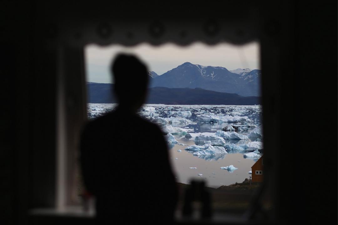 全球變暖致北極圈爆發炭疽 70多人入院。圖為格陵蘭一個居民望出窗外的冰川。