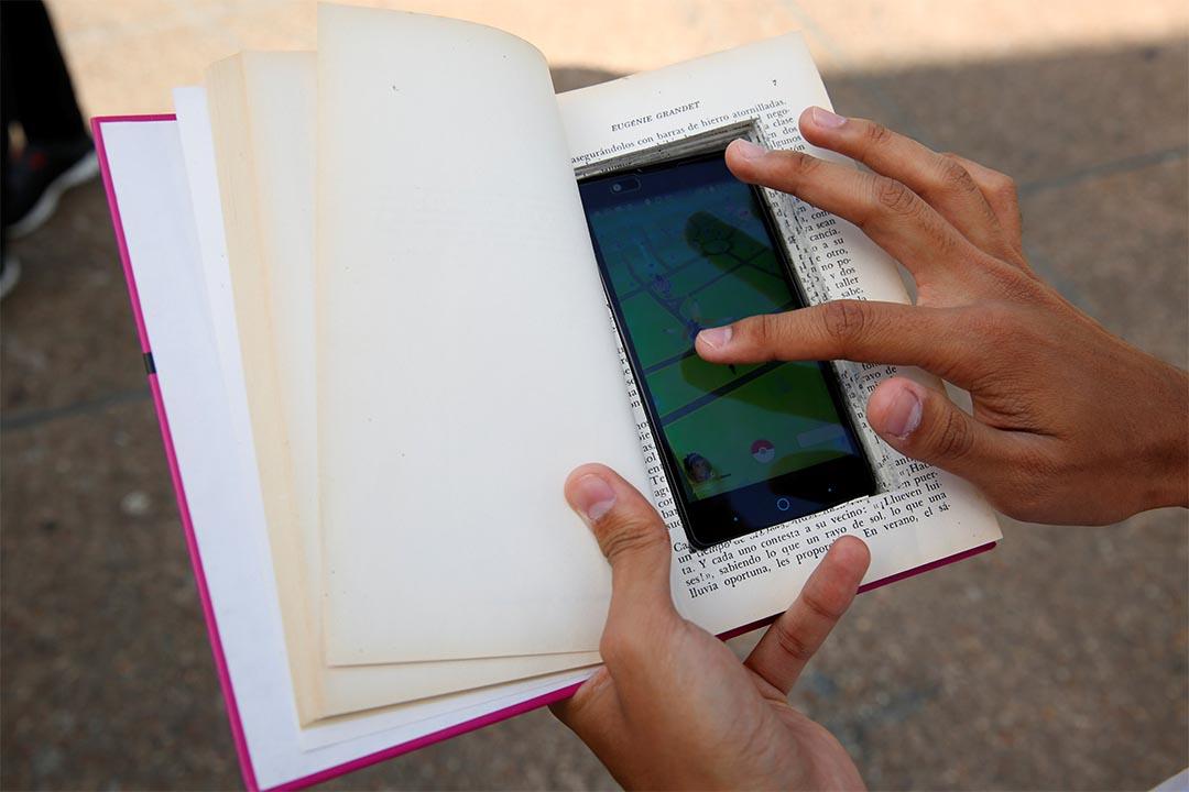 2016年8月9日,委內瑞拉卡拉卡斯,一個人把手提電話藏在書中玩