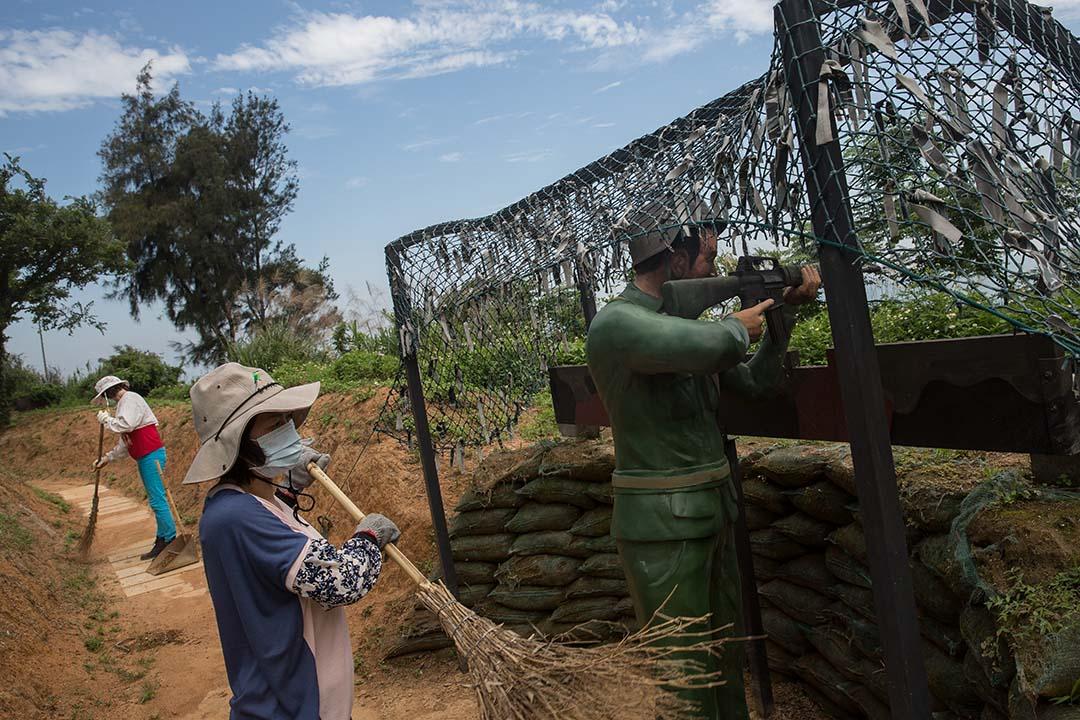 金門,與中國最接近的台灣島嶼。兩名工人正在打掃「站崗」的國民黨士兵雕像。
