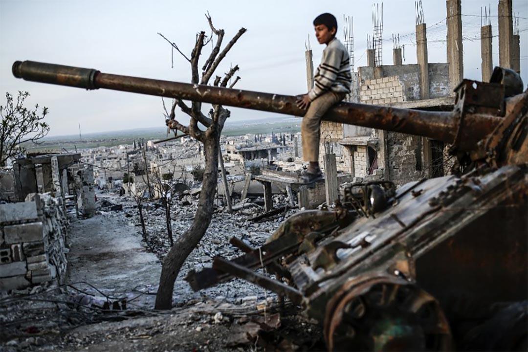 2015年3月27日,一個男孩坐在損毀的坦克上。