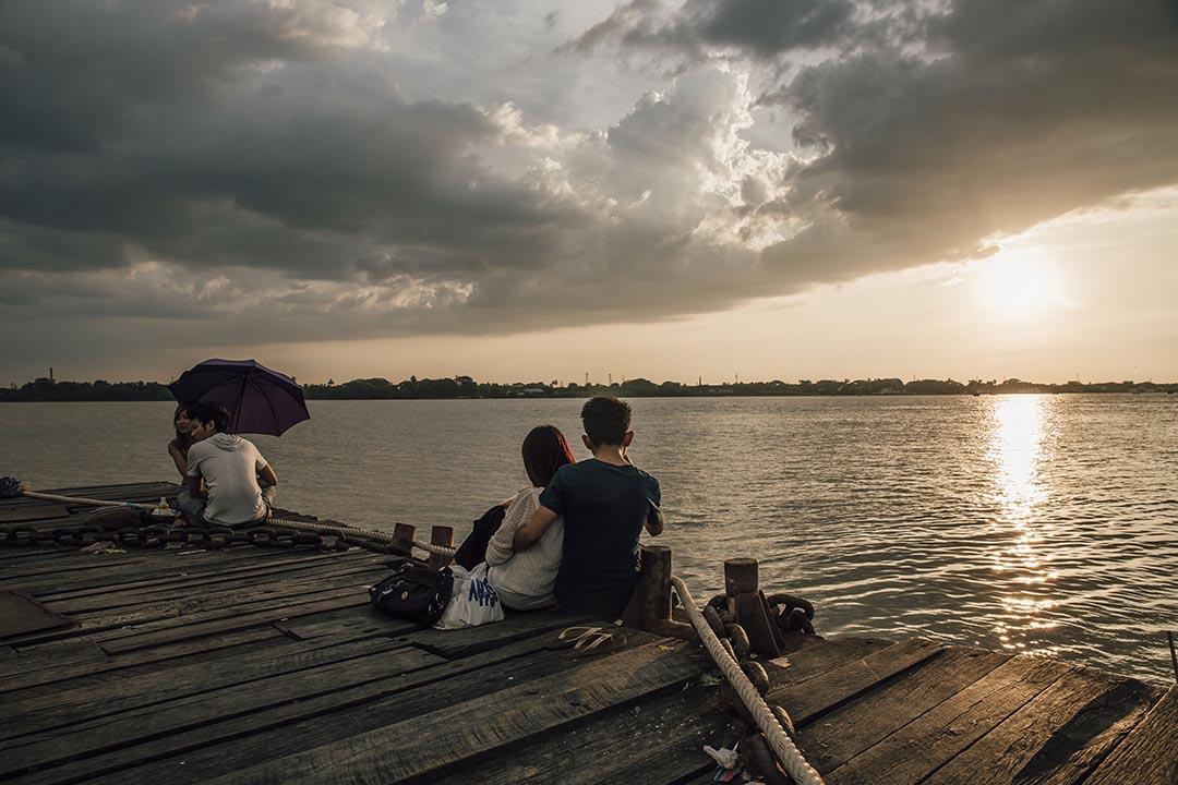 市民在緬甸河邊觀看日落。