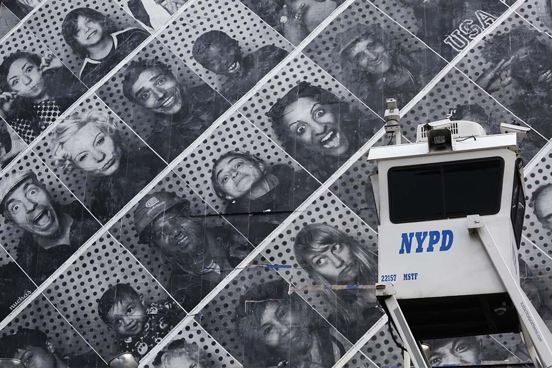 圖為美國紐約,一個監視器設在一幅印有不同人臉的牆。