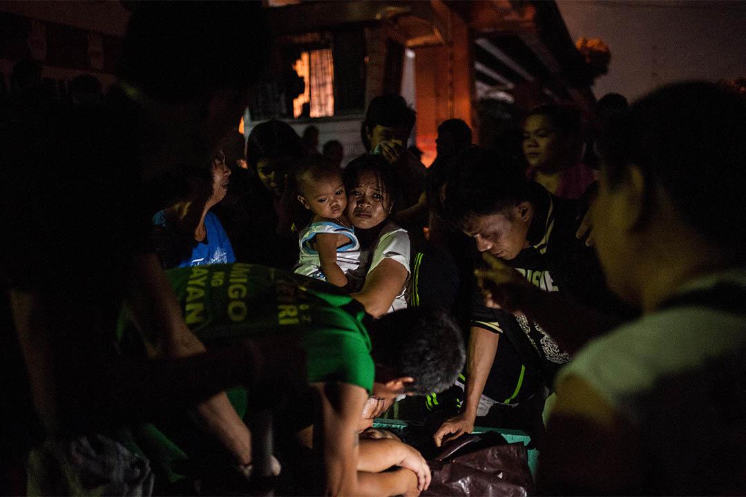 2016年8月17日,菲律賓馬尼拉,家屬圍著一個被疑為毒販者的屍體。