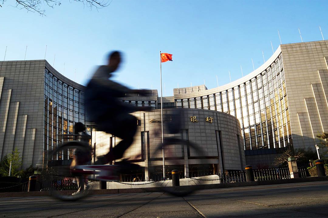 2014年4月4日,中國北京,一個市民騎著自行車從中國人民銀行辦公樓前駛過。