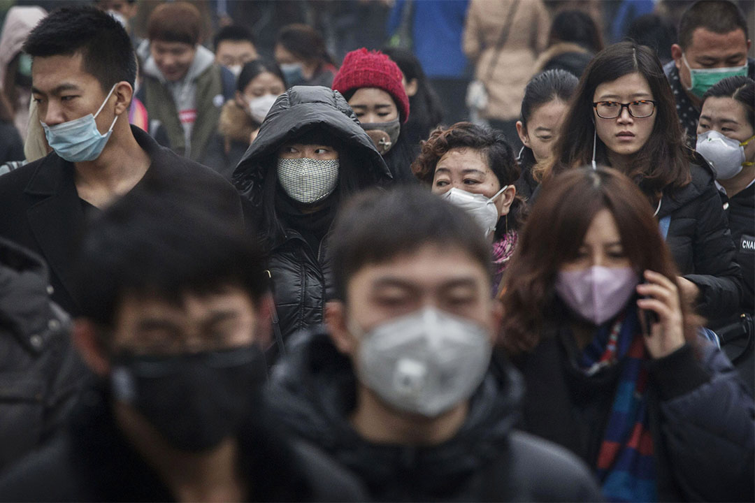 图为2015年12月9日,北京街头上人群戴着口罩上班。
