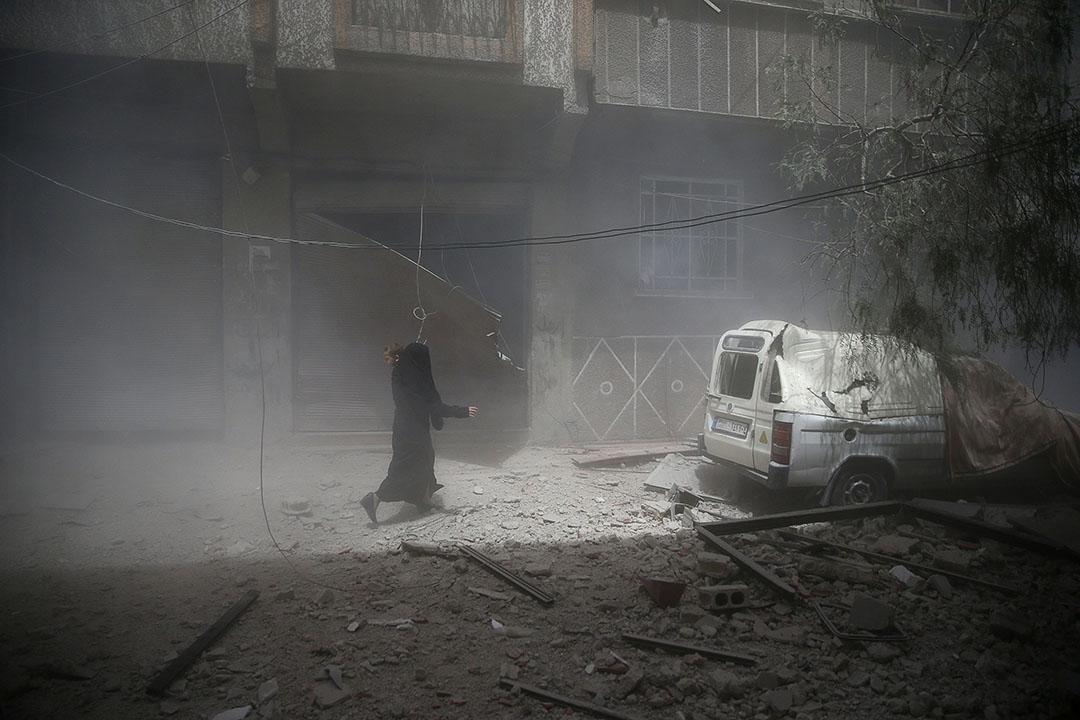 2016年8月20日,敘利亞大馬士革東部的杜馬鎮,一名婦女背著小孩走過受空襲後的街道。