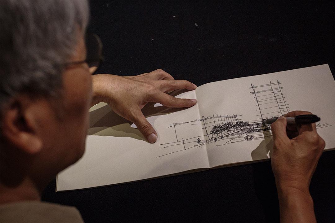 馮永基在紙上畫出建築意念。