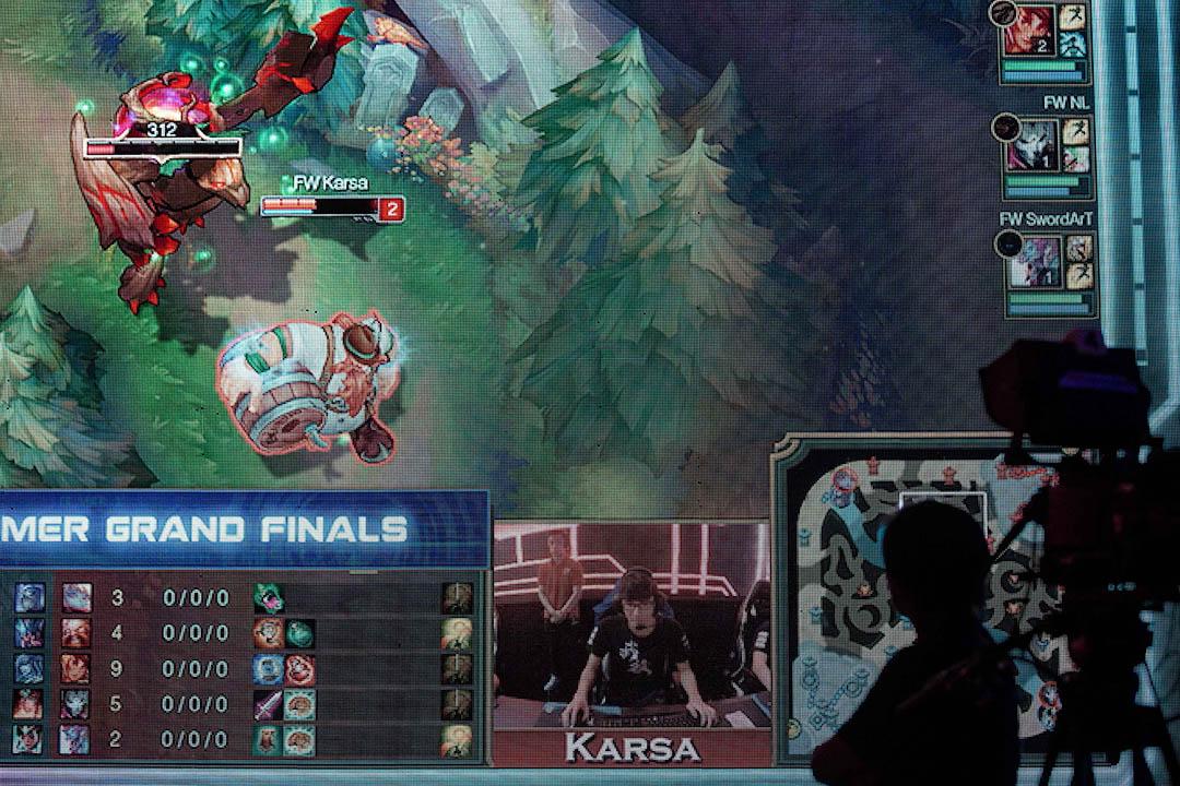選手坐在電腦前控制虛擬世界中的「英雄」進行對決。