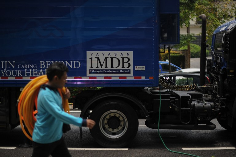 2016年3月14日,馬來西亞吉隆坡,一個工人走過印有1MDB標誌的海報。
