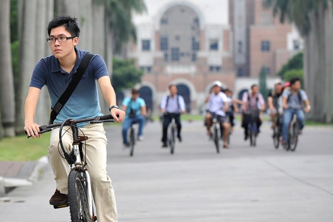 一名學生在台大校園裡騎單車。