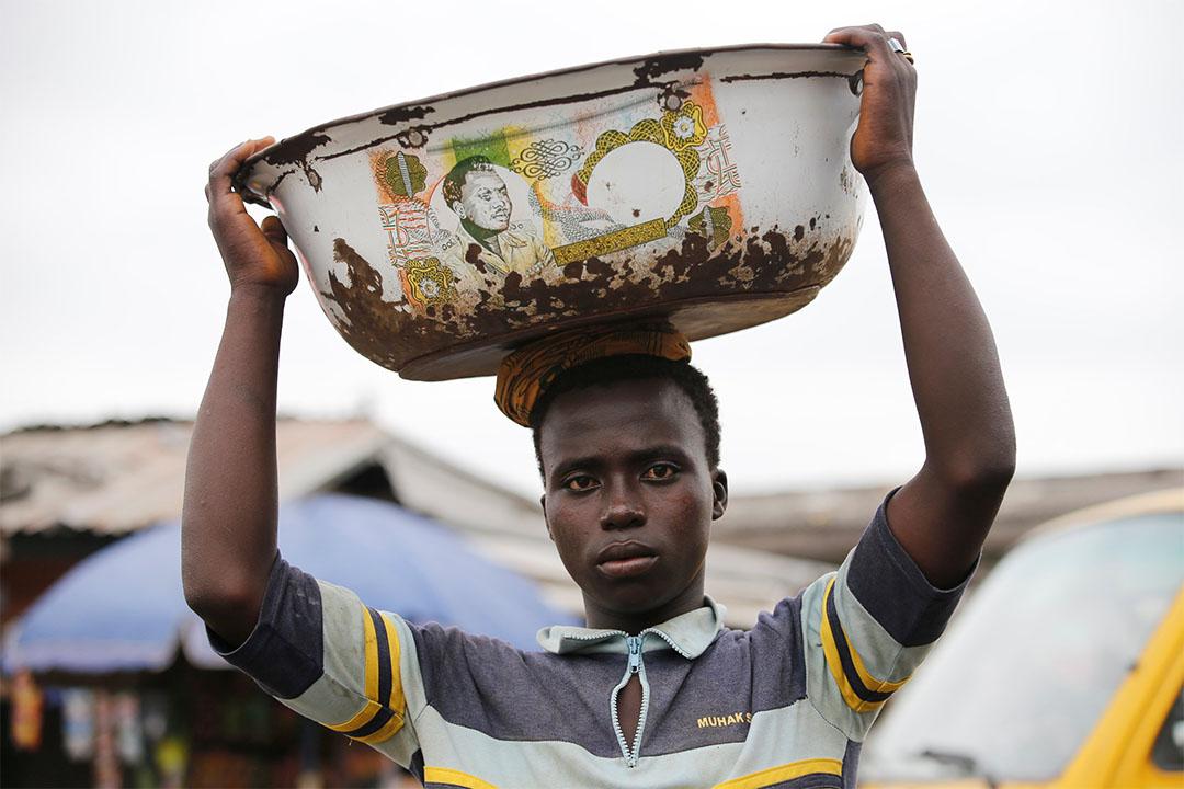 2016年8月16日,尼日利亞拉各斯一個市場內,一個男人用頭頂著盆。