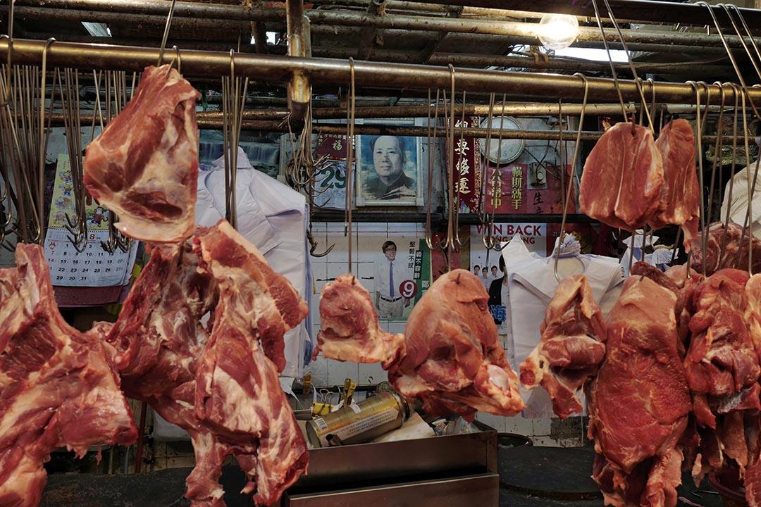 在肉店內,民主黨參選人的宣傳單張張貼了在毛澤東肖象之下。