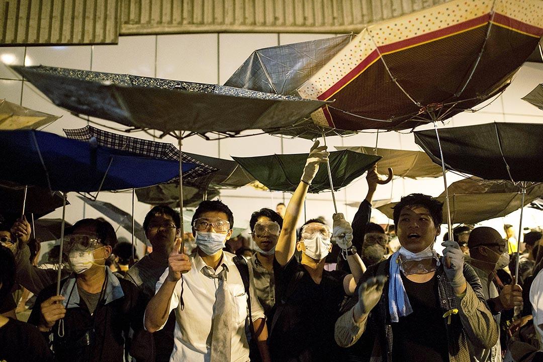 雨傘運動期間,示威者用雨傘擋住胡椒噴霧。圖為2014年10月14日,示威者佔領龍和道。