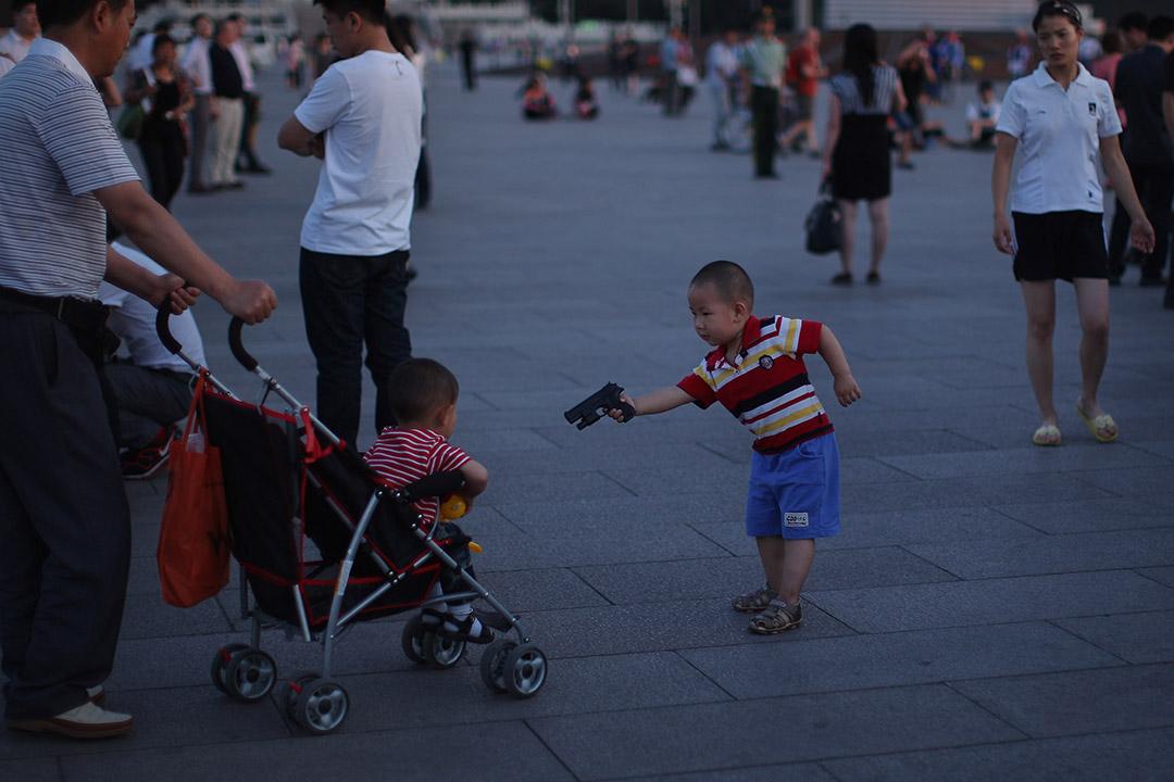 一名男童拿著玩具槍對著經過的幼兒比劃。
