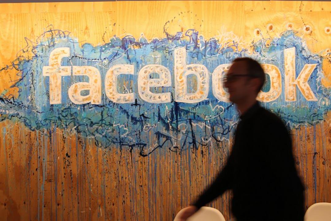 2015年10月22日,愛爾蘭,一個facebook員工走過其公司標誌。