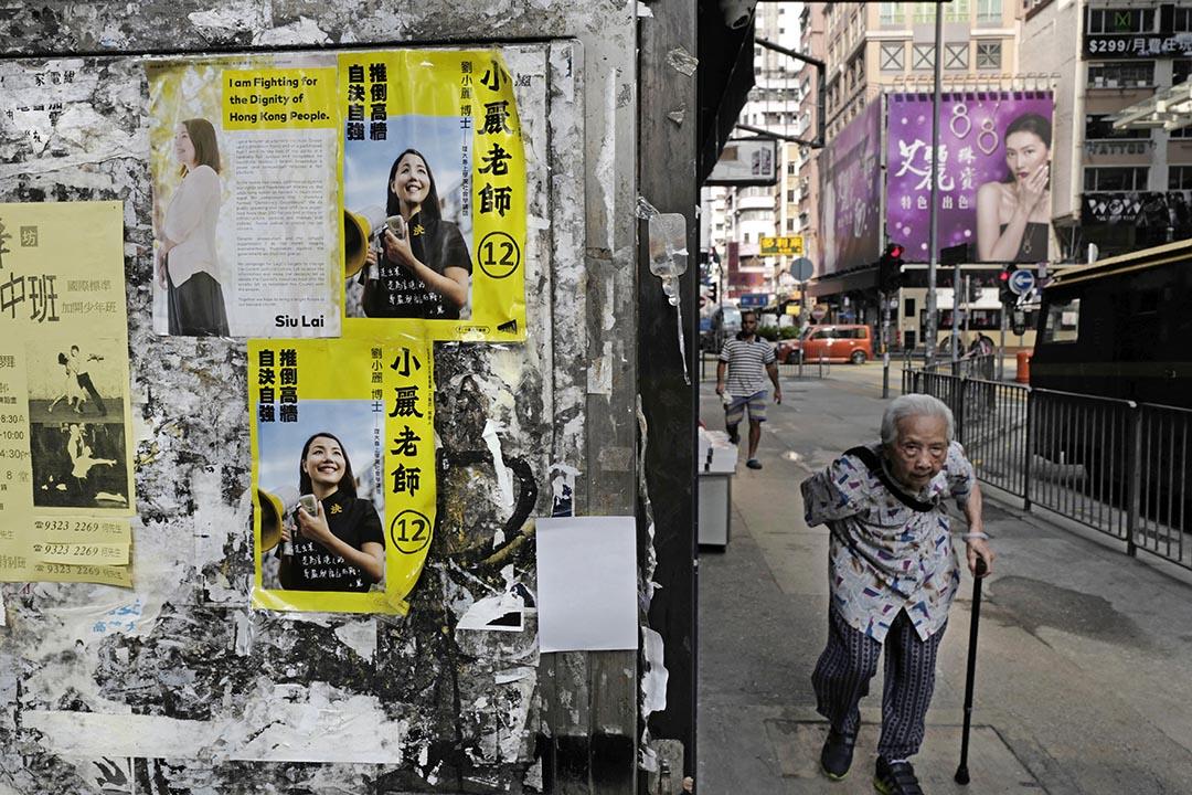 一名老人走過張貼著小麗民主教室宣傳單張的街道。