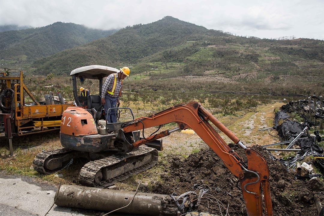 圖為2016年7月9日,一個工人正在清除被颱風吹塌的電線杆。