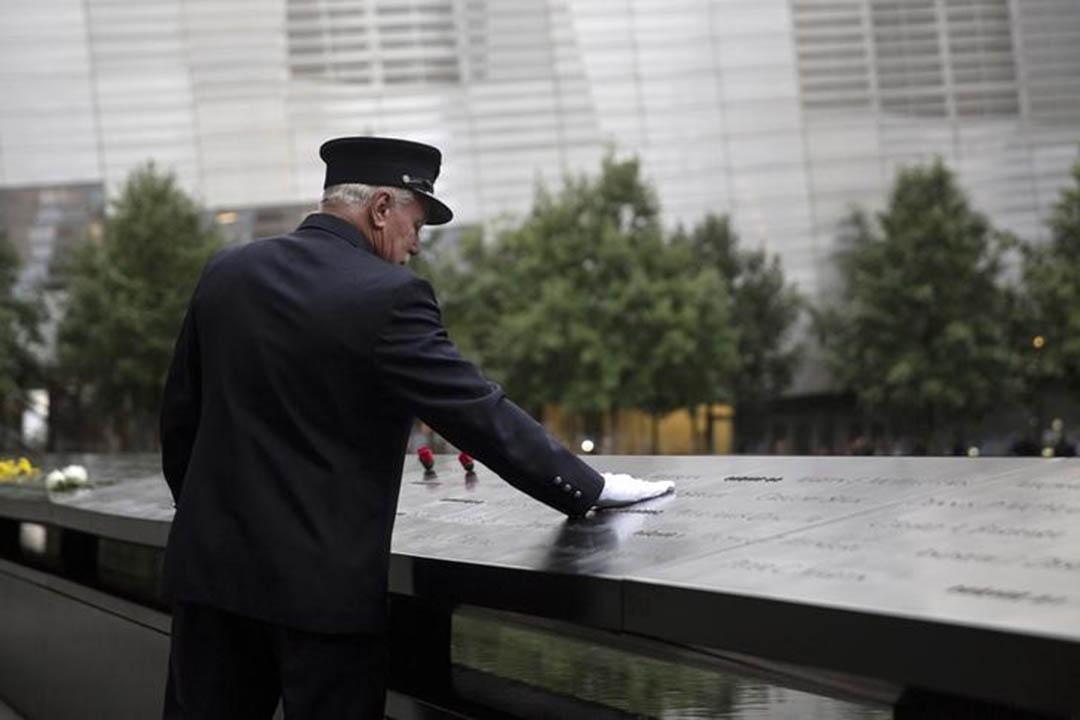 2015年9月11日,美國紐約,一個消防員把手放在9.11國家紀念博物館的紀念碑上。