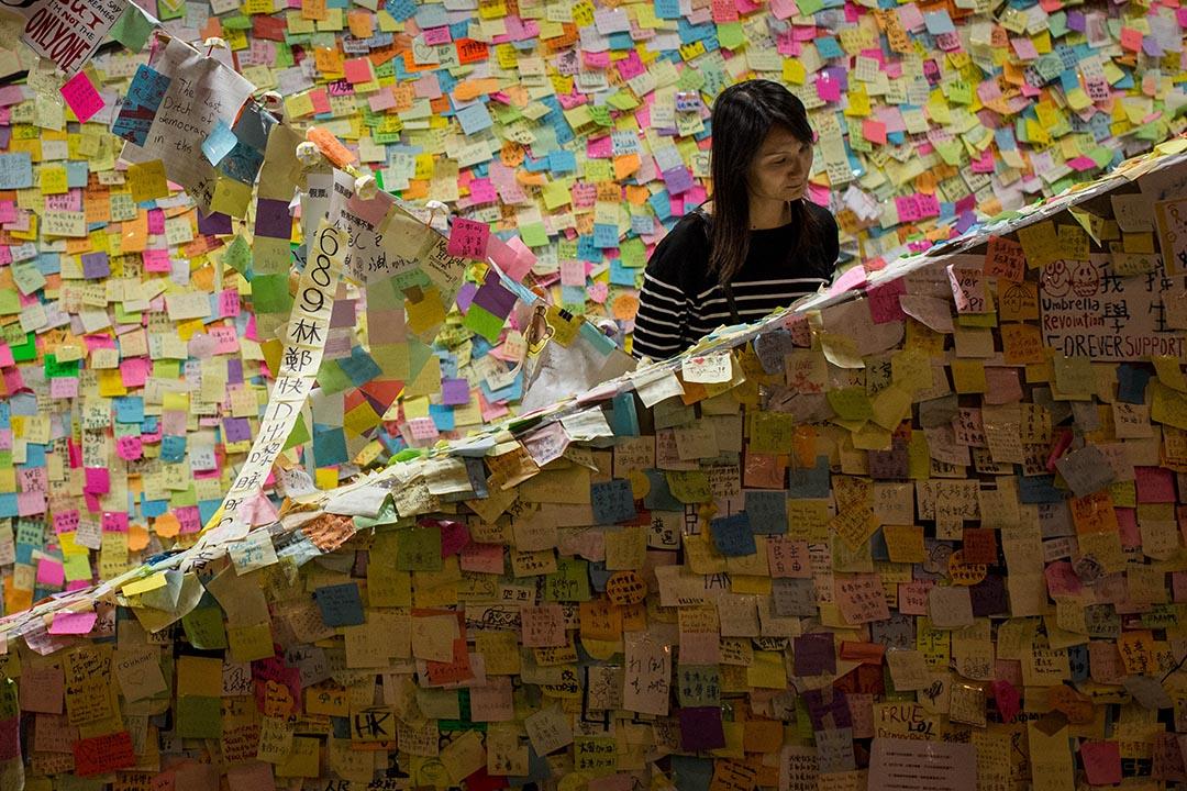 2014年10月16日,雨傘運動期間,一個女士在「連儂牆」看人們寫下的字句。