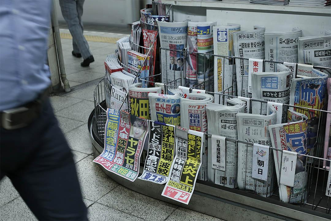 2016年8月3日,日本東京,人們走經一個報攤。