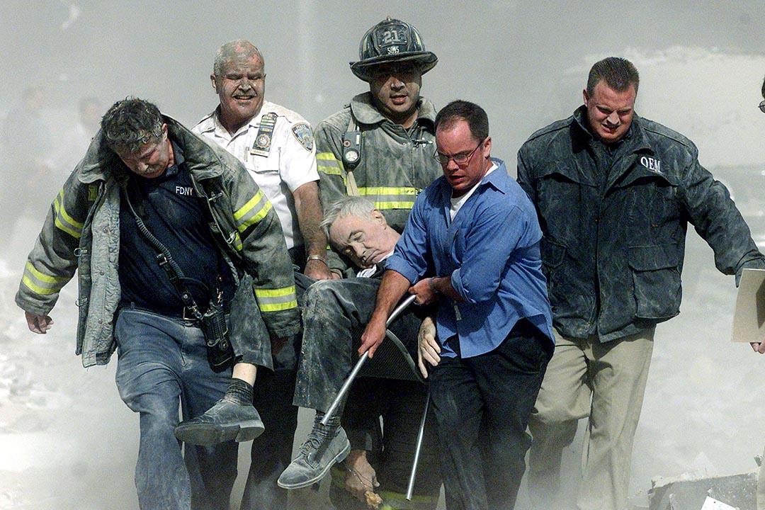 2001年9月11日,美國紐約,救援人員在911恐怖襲擊現場將受傷的消防局專職隨行牧師米卡爾·喬治(Father Mychal Judge)抬出廢墟。