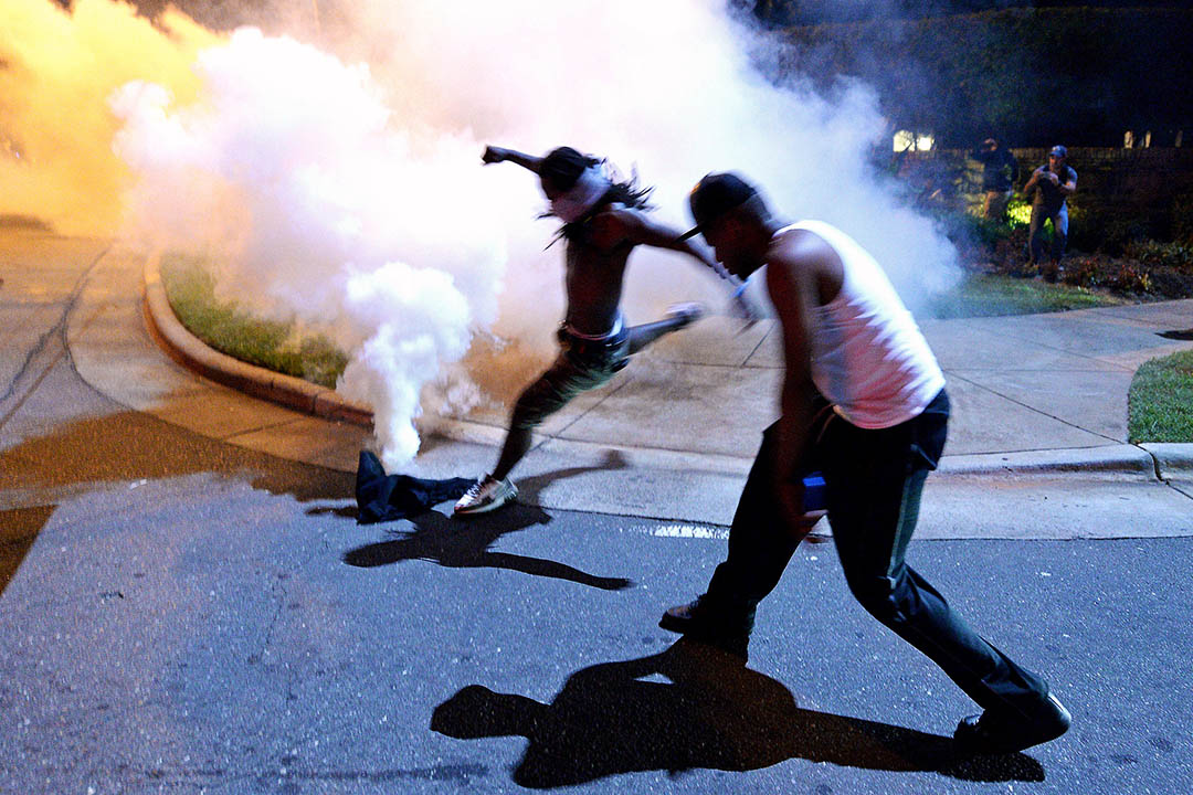 示威者用腳踢走警方發射的催淚彈。