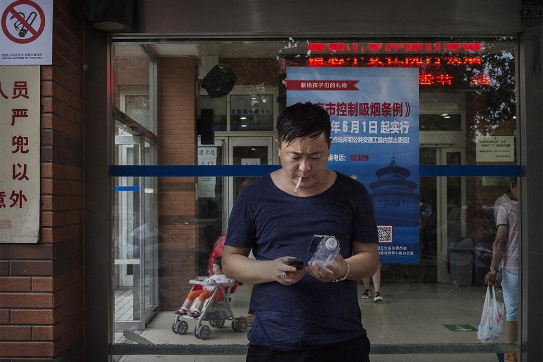 2015年6月1日,中國北京,一個男人站在禁煙海報前抽煙。