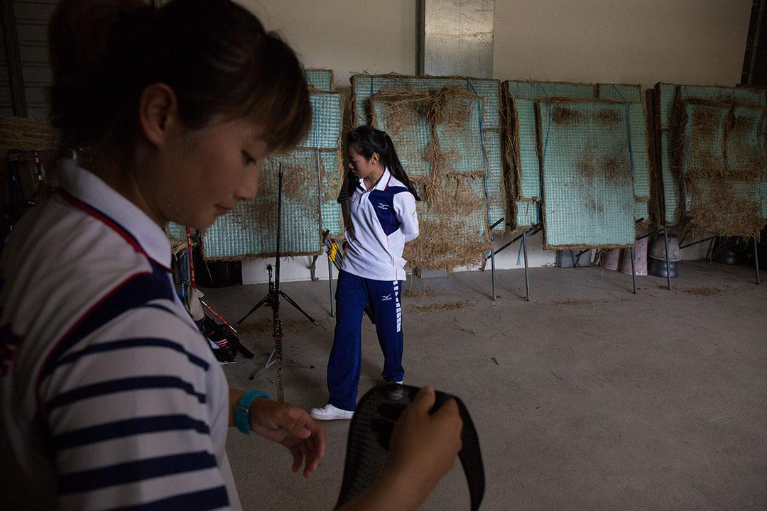 林詩嘉與譚雅婷在富禮國中射箭練習棚裡著裝。