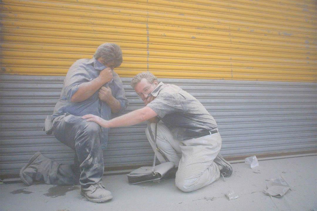 2001年9月11日,世貿中心倒塌後,兩名市民在濃煙中掩著面。