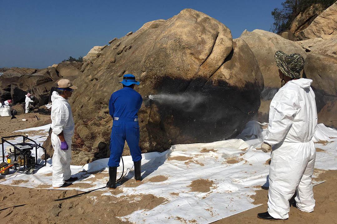 清潔人員正在清洗岸邊被油污覆蓋的岩石。