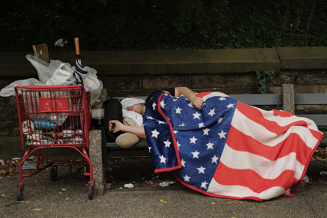 紐約市的布魯克林一名露宿者在公園的長椅上睡覺。