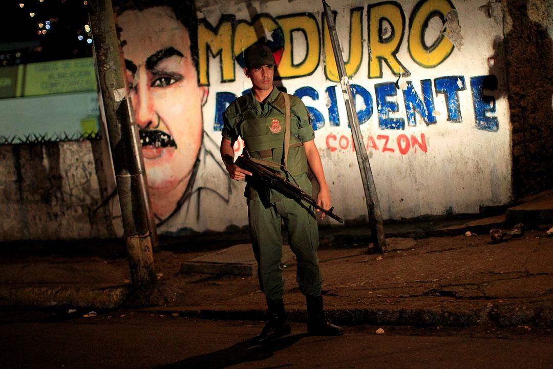 委內瑞拉加拉加斯貧民窟,士兵巡邏時站在描繪委內瑞拉總統馬杜羅的壁畫前。