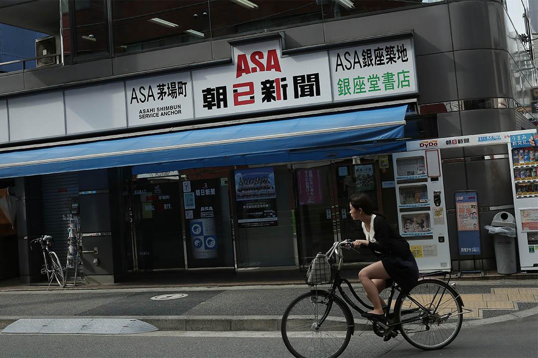 2016年8月3日,日本東京,一個女士騎着單車駛過朝日新聞茅場町辦公室。