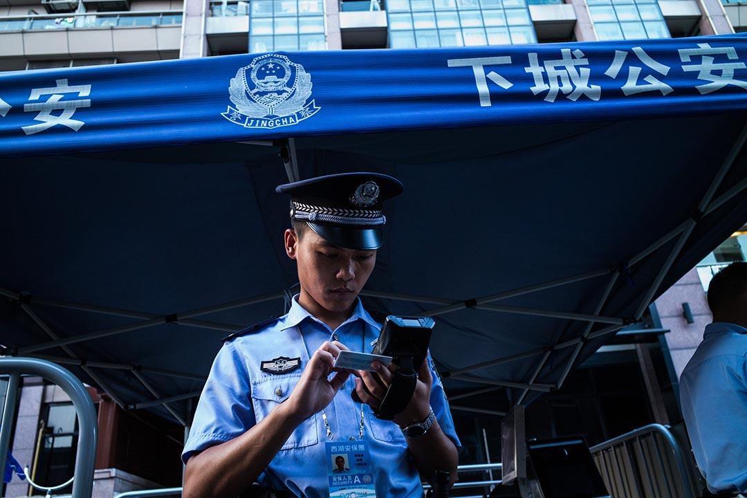公安在檢查進入封鎖區的市民的身分證。