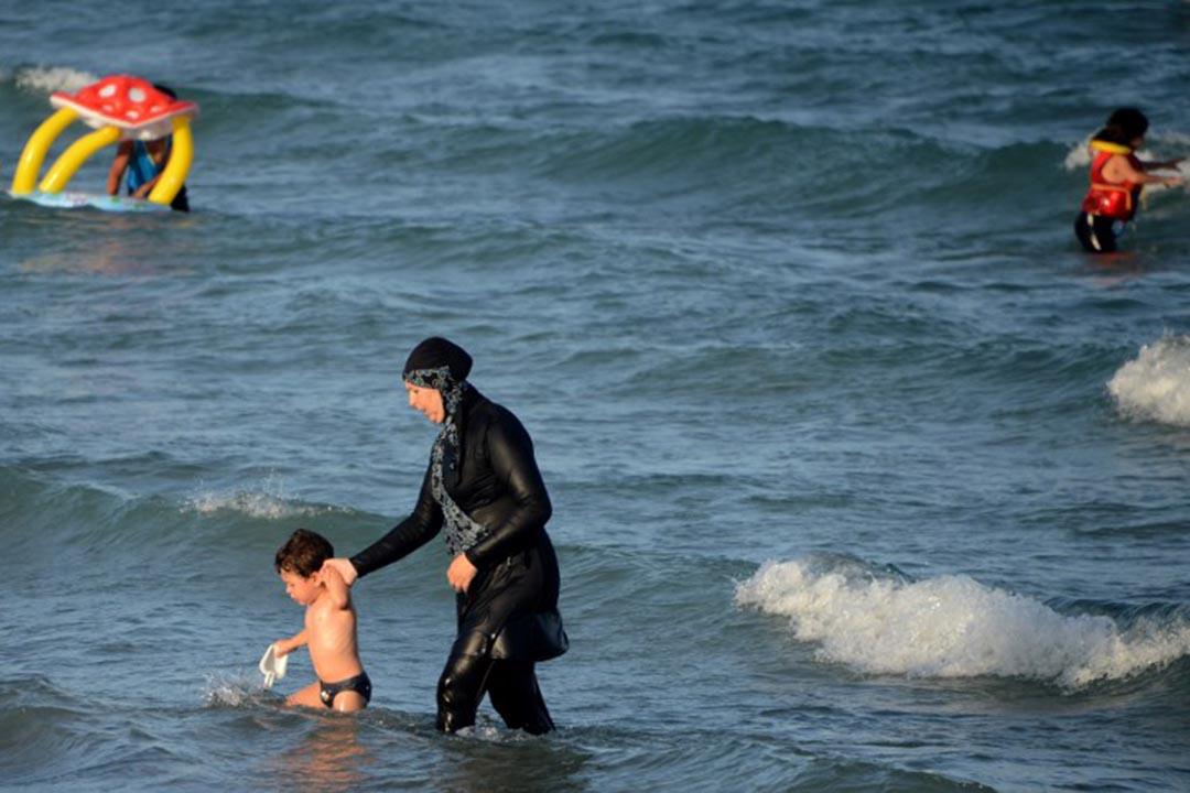 一名穿burkini婦人在海灘帶著孩子在水中走路。