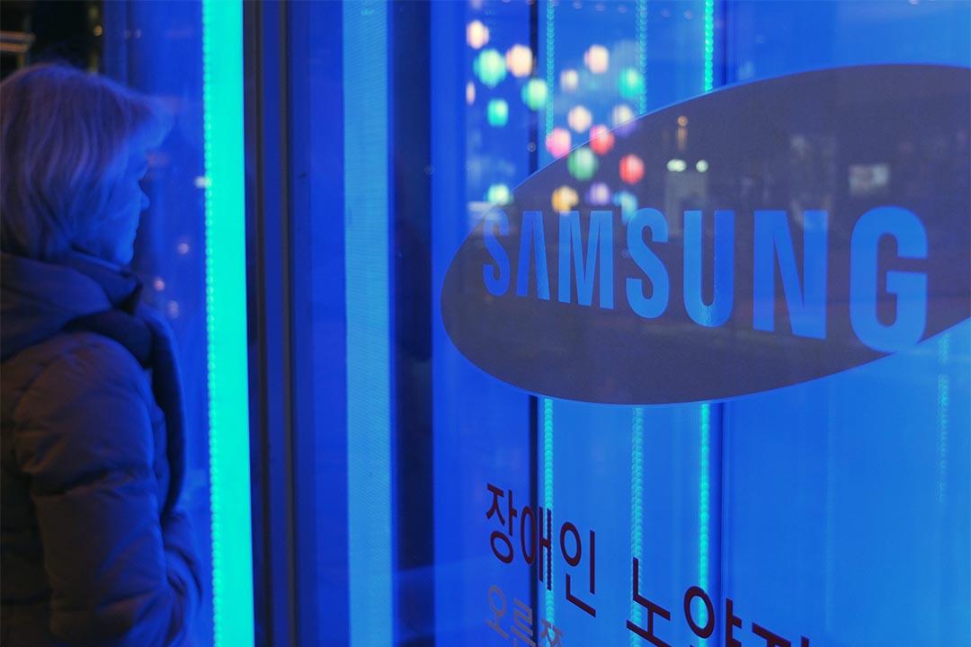 一位女士站在Samsung總部大門旁。