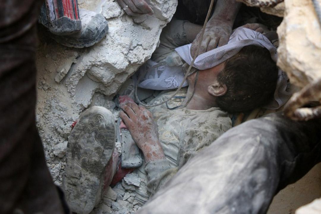 2016年10月11日,敘利亞阿勒頗,敘利亞反政府武裝控制區域遭俄羅斯空襲後,一名小孩被埋在瓦礫中。