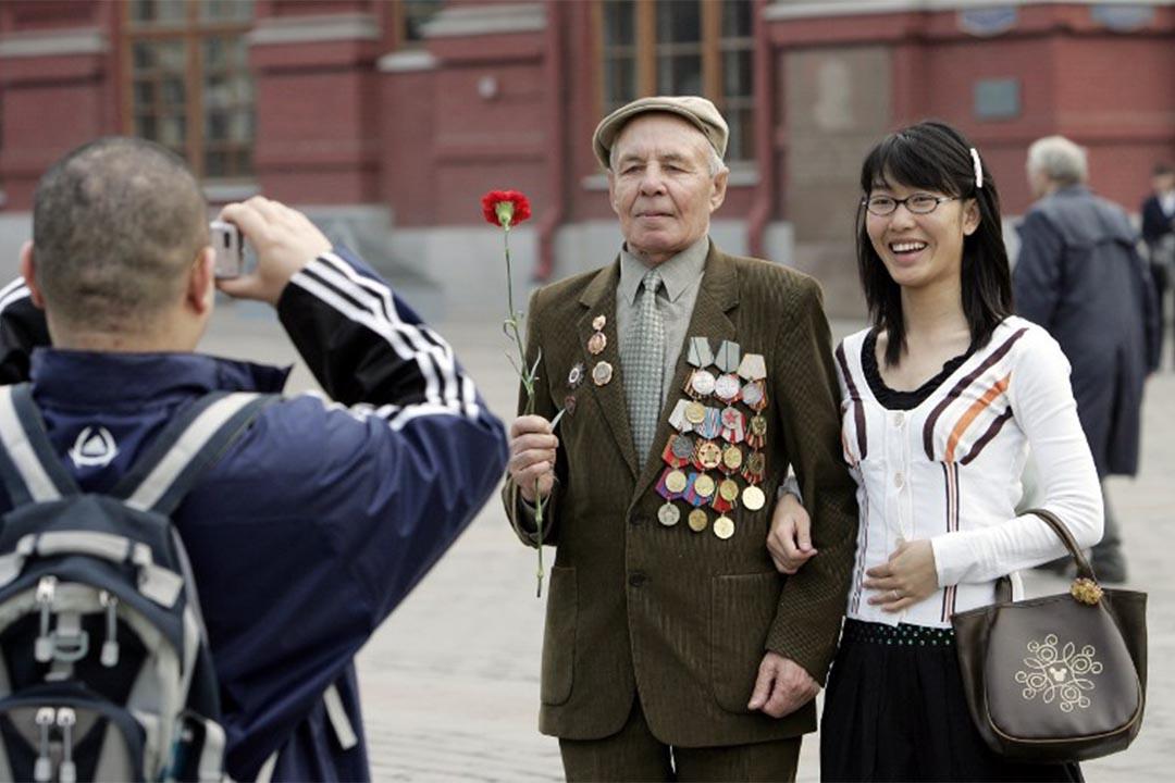 圖為俄羅斯莫斯科,中國遊客跟俄羅斯退役軍人合照。