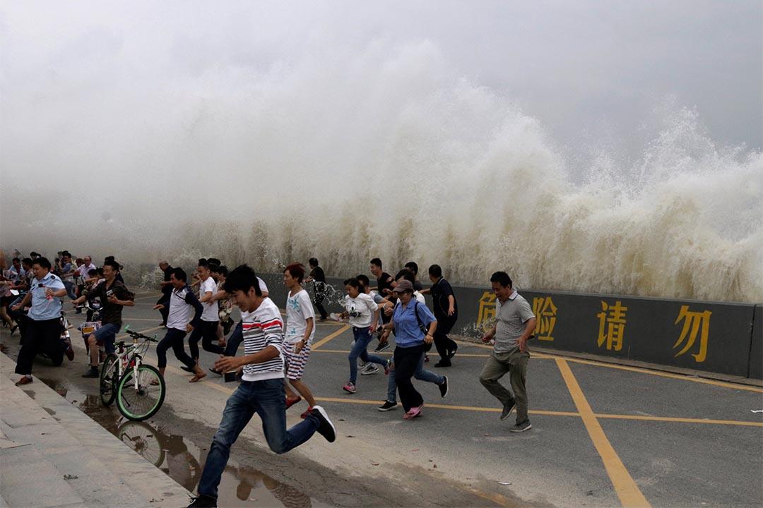 2016年10月3日,中國杭州錢塘江,人們躲避巨浪。