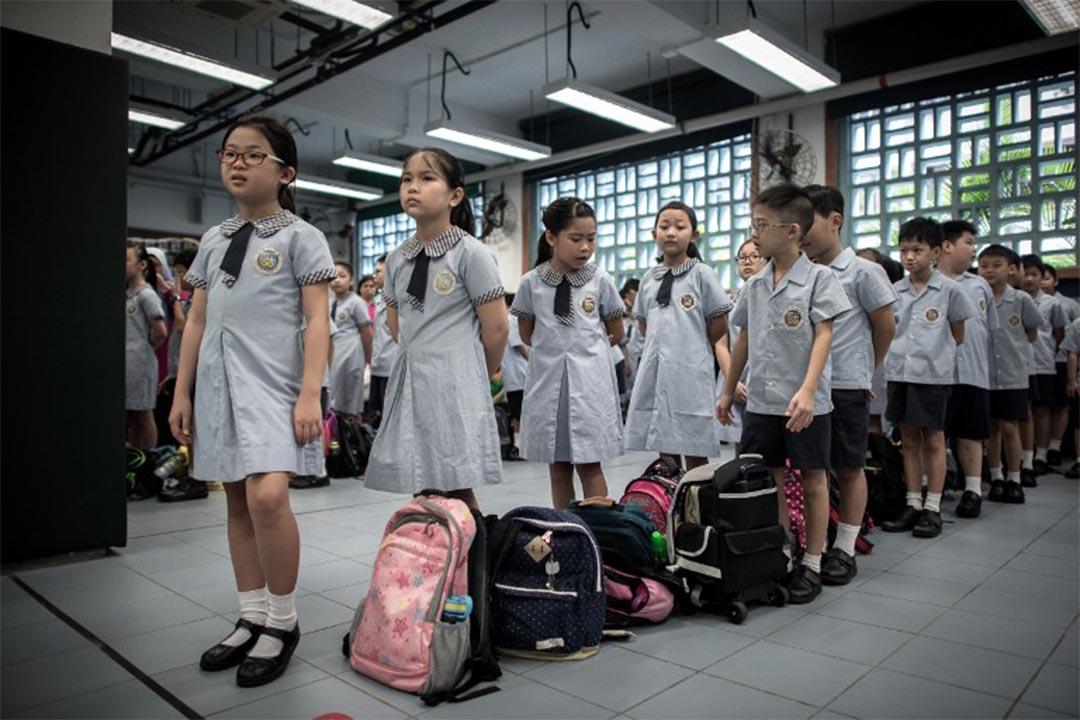 圖為一群小學生在學校禮堂排隊。