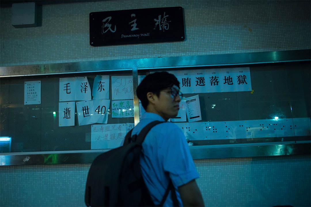 落選的研究生巫堃泰走過香港大學的民主牆,牆上有斥責朱科的字句,也有為朱科解釋的張貼物。