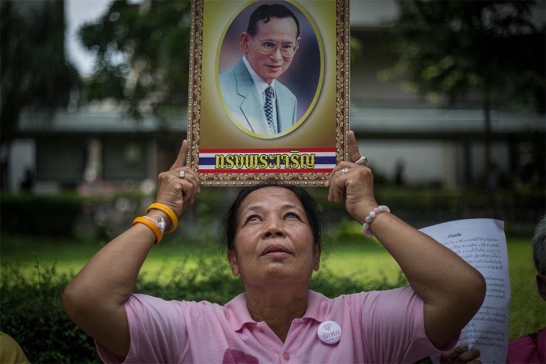 一個女士手持著泰王普密蓬的肖像。