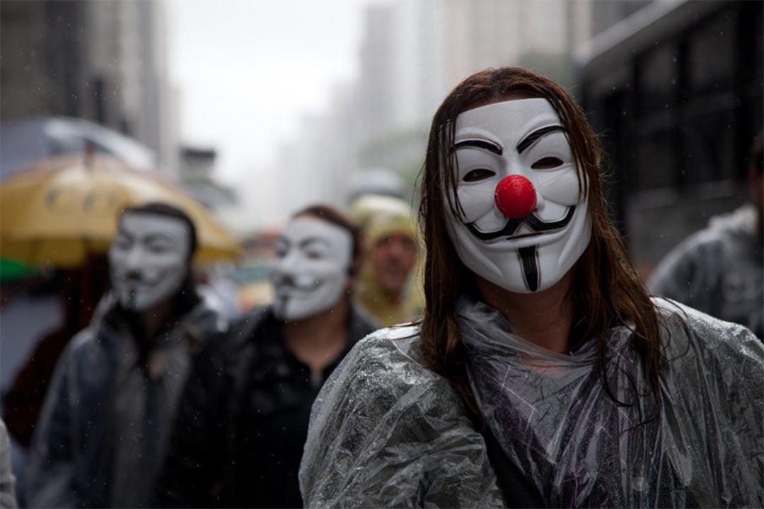 圖為巴西聖保羅,人們戴著V煞面具遊行。