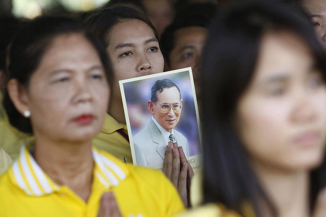 泰國民眾手持泰王普密蓬的肖像。